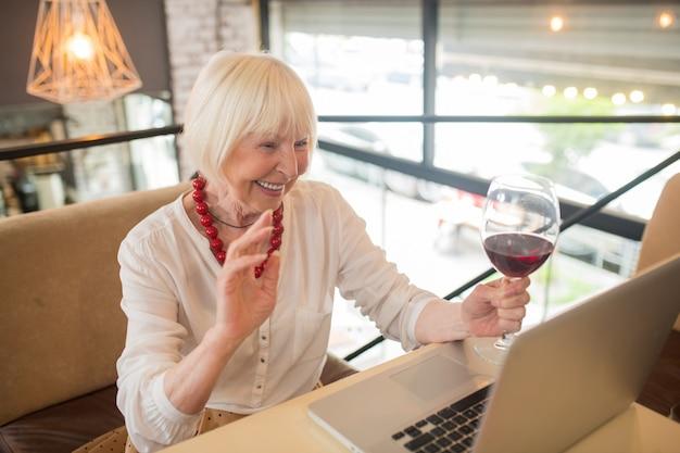 Video-oproep. elegante senior vrouw die wat wijn drinkt en via video praat