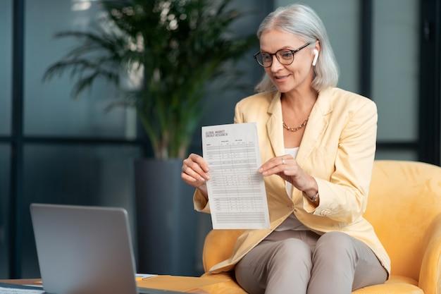 Video-oproep. fijne knappe vrouw die voor een laptop zit en een document laat zien tijdens de videoconferentie