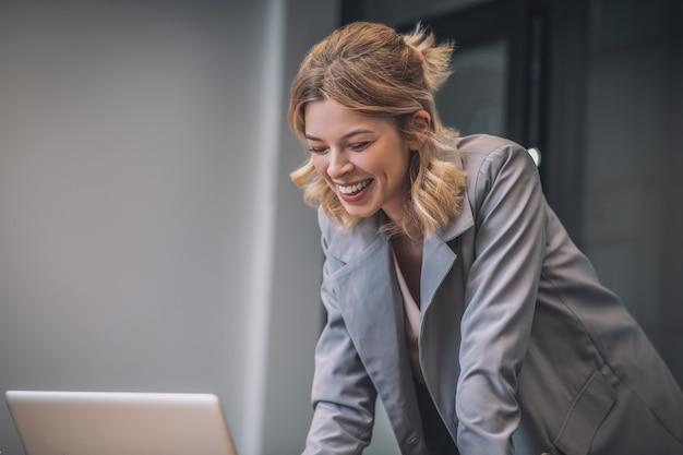 Video-oproep. jonge gelukkig lachende vrouw in pak staande in de buurt van laptop praten door videocommunicatie in kantoor