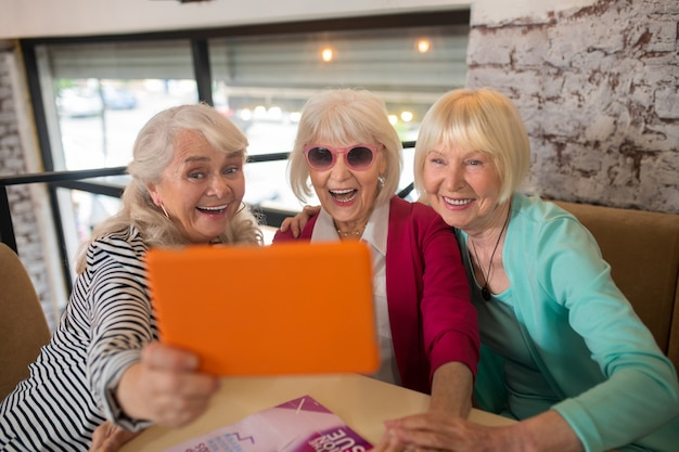 Video-oproep. knappe bejaarde dames die een videogesprek voeren en er opgewonden uitzien
