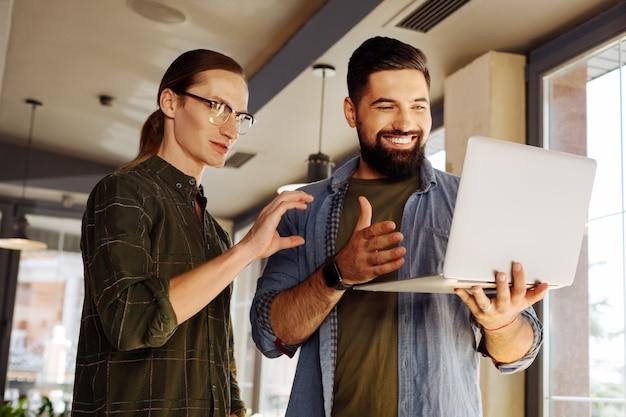 Video-oproep. vrolijke gelukkige mannen die voor het laptopscherm staan terwijl ze op video via internet spreken