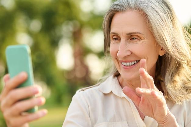 Video-oproep. vrolijke volwassen mooie vrouw die minzaam naar het smartphonescherm kijkt en communiceert via een videogesprek in het park op zomerdag
