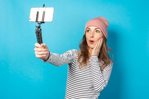 Videoblogger van de jonge vrouw maakt foto's van zichzelf aan de telefoon tijdens het uitzenden op een blauw oppervlak