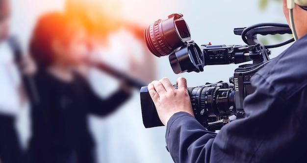 Videocameraexploitant die met zijn materiaal werkt