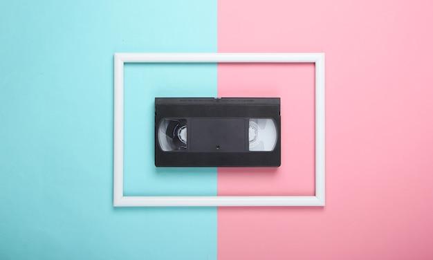 Videocassette op roze blauw pastel oppervlak met wit frame