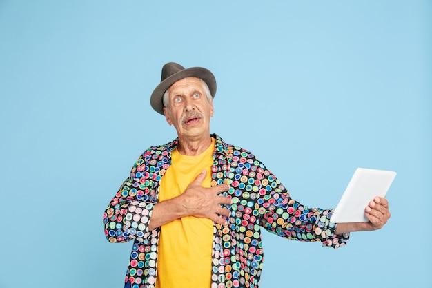 Videochat met behulp van tablet, geschokt. portret van senior hipster man in stijlvolle hoed op blauw. tech en vrolijk ouderen lifestyle concept