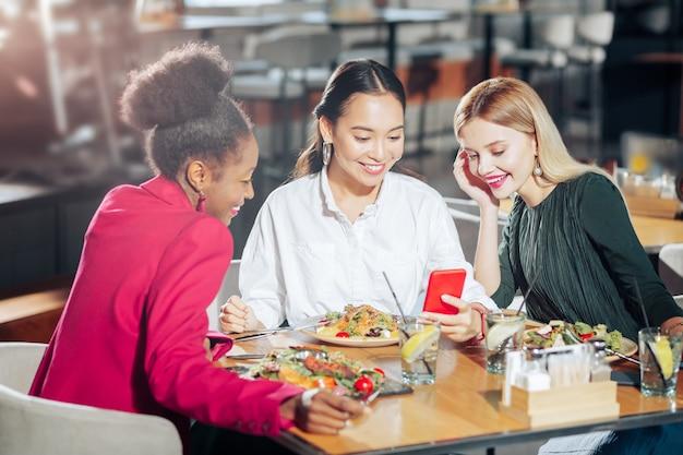 Videochatten drie zakenvrouwen die smakelijke salades eten en videochatten met een vriend