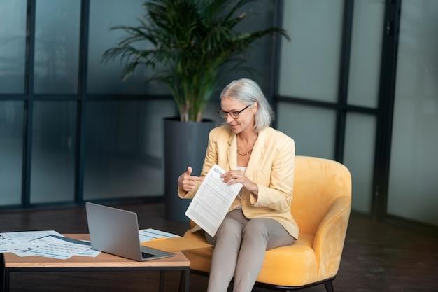 Videoconferentie. tevreden blanke zakenvrouw die deelneemt aan een videoconferentie terwijl ze aan de tafel in haar kantoor zit