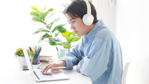 Videoconferentie, thuiswerken, aziatische man die videogesprek voert met virtueel web, contact opnemen met teamconferentie op laptopcomputer thuis, praten op internet, online consultatiebedrijf