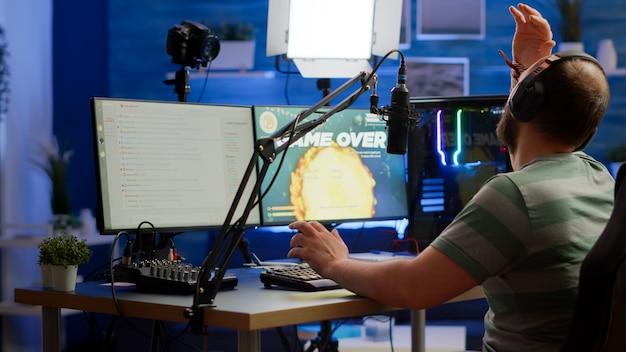 Videogame-streamer verliest online videogame-competitie met een professionele headset die praat tijdens streamchat. trieste gamer die krachtige computer gebruikt voor gametoernooien 's avonds laat met space shooter gam