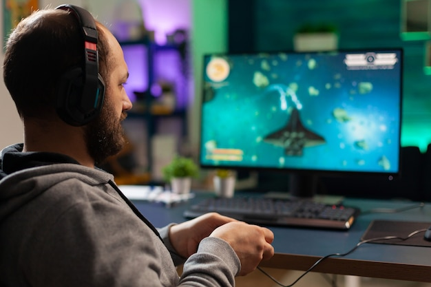 Videogamer die grafische cyberspace speelt terwijl hij op een gamingstoel zit met behulp van draadloos technologienetwerk. man streamt virale videogames voor de lol met koptelefoon en joystick voor online kampioenschap