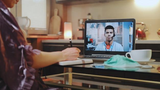 Videogesprek op computer met collega van gemengd ras thuis op quarantaine