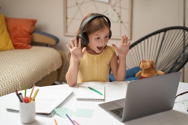 Videogesprek voeren met een gelukkig klein kaukasisch meisje in een koptelefoon die online zwaait en