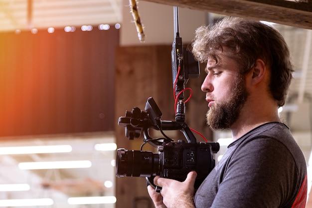 Videograaf die een film of televisieprogramma maakt in een studio met een professionele camera, backstage