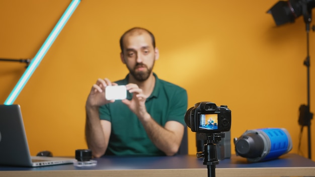 Videograaf die mini led-licht vasthoudt tijdens het opnemen van een recensie voor vlog. professionele studiovideo- en fotoapparatuurtechnologie voor werk, fotostudio social media ster en influencer