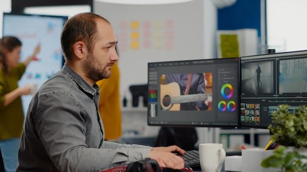 Videograaf die naar camera kijkt die lacht op een creatieve startup-werkplek