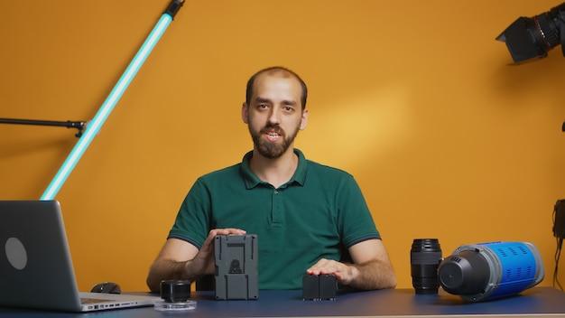 Videograaf die professionele recensie opneemt voor oplaadbare batterijen. moderne technologie van het v-lock-type, online distributie van sterbeïnvloeders op sociale media