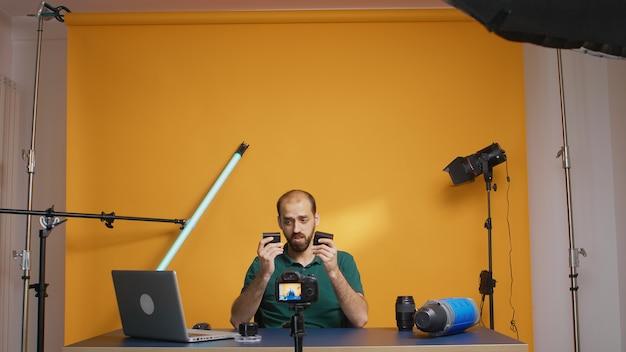 Videograaf opname beoordeling van oplaadbare batterijen voor camera. elektronica en camera-apparatuur van het type np-f, uitrusting voor videografie, maker van sociale media voor online distributie