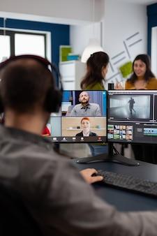 Videograafmedewerker die videoconferentie heeft met een headset die klantfilm bewerkt en feedback krijgt over een commercieel project