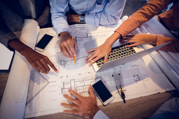 Vier architecten bespreken blauwdrukken in vergadering
