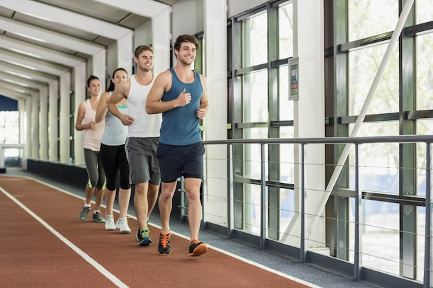 Vier atletische vrouwen en mannen die zich uitstrekt over de atletiekbaan