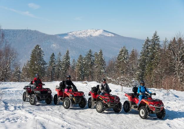 Vier atv-rijders op offroad-quads boven op de berg in de winter
