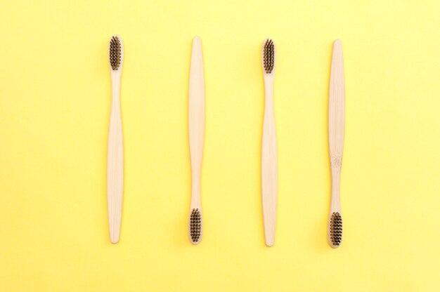 Vier bamboe tandenborstels op een gele achtergrond. tandheelkunde.