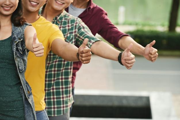 Vier bebouwde jongeren die op een rij tonen beduimelt omhoog gebaar en gelukkig glimlachen