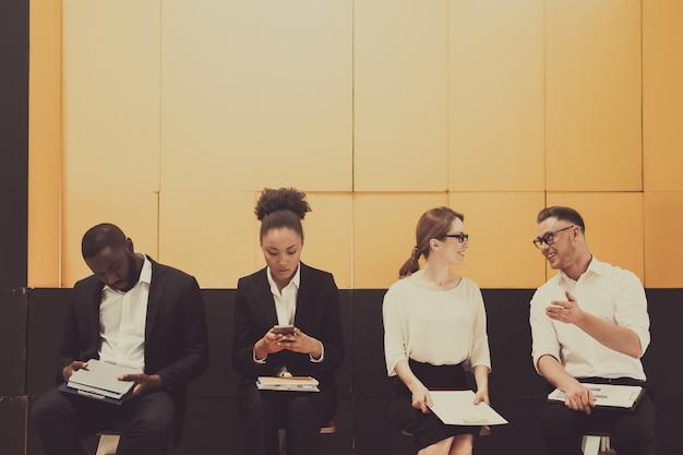 Vier bezige managers die op stoelen in bureau zitten.