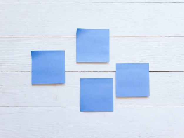 Vier blauwe papieren stickers op een witte houten bordmuur.