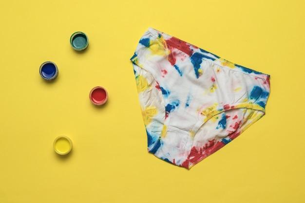 Vier blikken verf en een stropdas kleurstof slipje op een gele achtergrond. gekleurd ondergoed in huis.