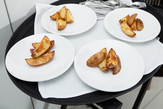 Vier borden met plakjes heerlijke gebakken aardappelen.
