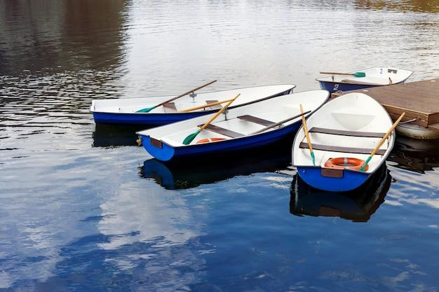 Vier boten op de rivier. blauwe oude boten op de pier. boten met roeispanen.