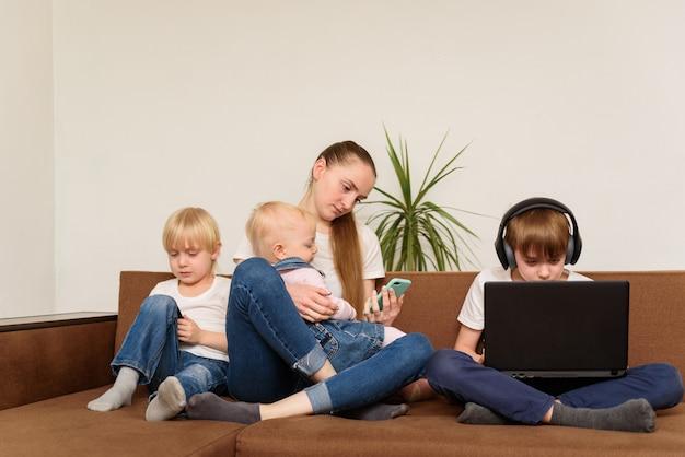 Vier broers en zussen zitten op de bank en gebruiken laptop en telefoons. generatie alpha concept