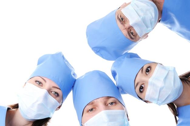 Vier chirurgenhoofden in maskers die samen een cirkel maken