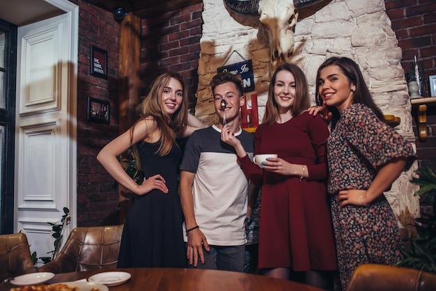 Vier coole tieners dragen casual kleding poseren voor de camera in een stijlvolle met jacht lodg