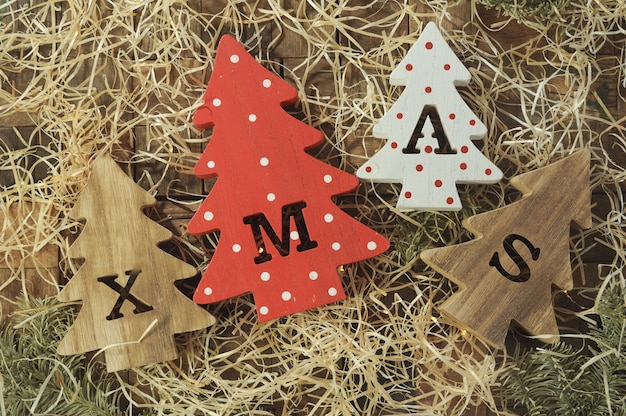 Vier decoratieve houten kerstbomen met uitgesneden letters xmas en delicatesse in de vorm van kleine botten voor huisdieren. bovenaanzicht. horizontaal.