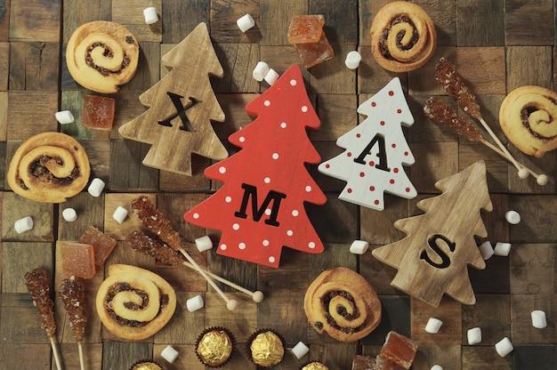 Vier decoratieve houten kerstbomen met uitgesneden letters xmas en kerstsnoepjes.