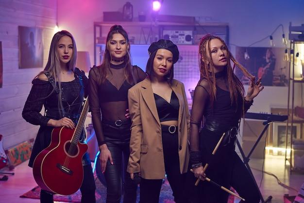 Vier deelnemers van moderne meidenband poseren in geluidsopnamestudio