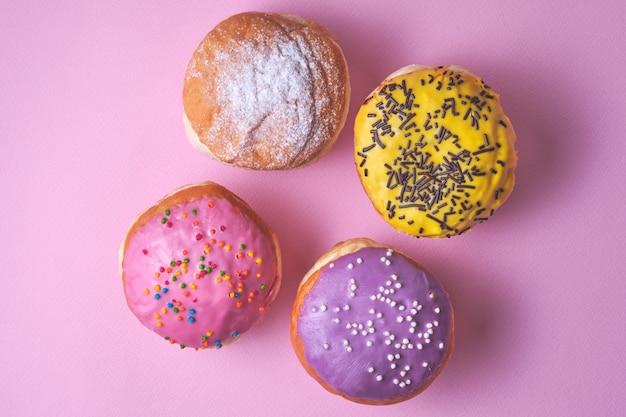 Vier donuts met gekleurde glazuur op een roze papier achtergrond.