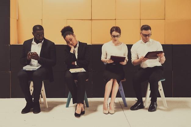Vier drukke managers zitten op stoelen in het kantoor.