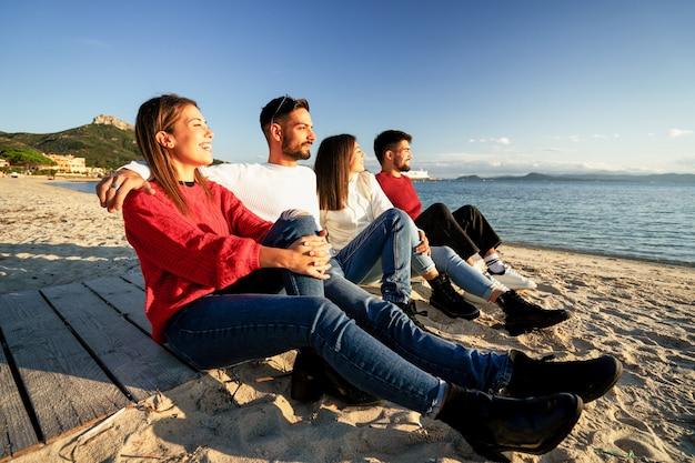 Vier duizendjarige vrienden die op een promenade van een strand in een badplaats zitten te kijken naar de ondergaande zon
