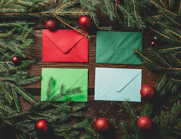 Vier enveloppen naast kerstversiering op een tafel