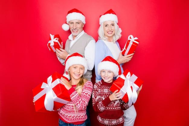 Vier familieleden - opgewonden broers en zussen en getrouwd ouder koppel van opa en oma met cadeautjes, in gebreide schattige traditionele x mas-kostuums, geïsoleerd op de rode ruimte, geniet van, stralende glimlach