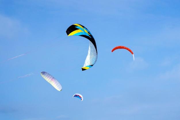 Vier felgekleurde sportvliegers voor vliegeren of snowkiten tegen de blauwe lucht