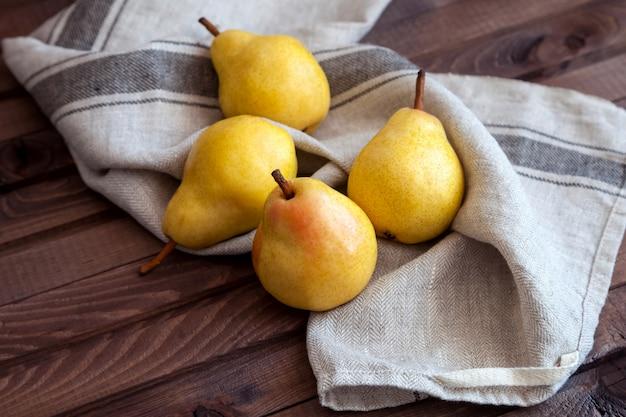 Vier gele peren op de tafel. rustieke stijl