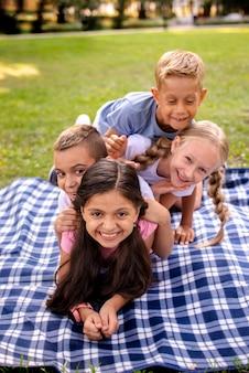 Vier gelukkige kinderen die op deken liggen