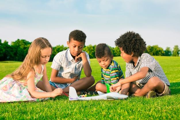Vier gelukkige kinderen spelen met vliegtuigspeelgoed en schilderen