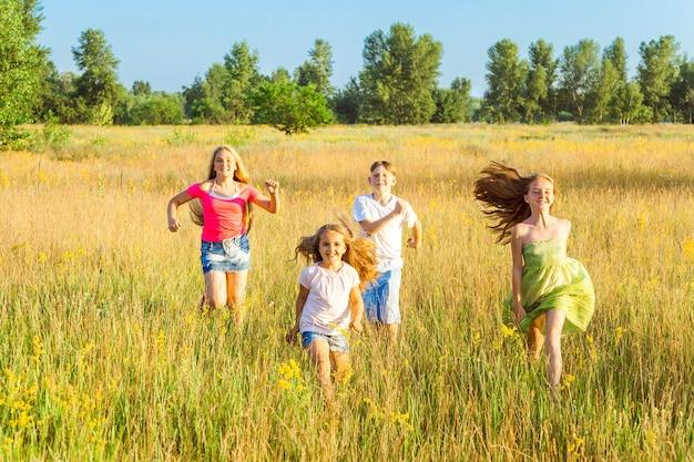 Vier gelukkige mooie kinderen rennen spelen samen in de mooie zomerdag. springen en kijken naar de camera met geluk en brede glimlach.