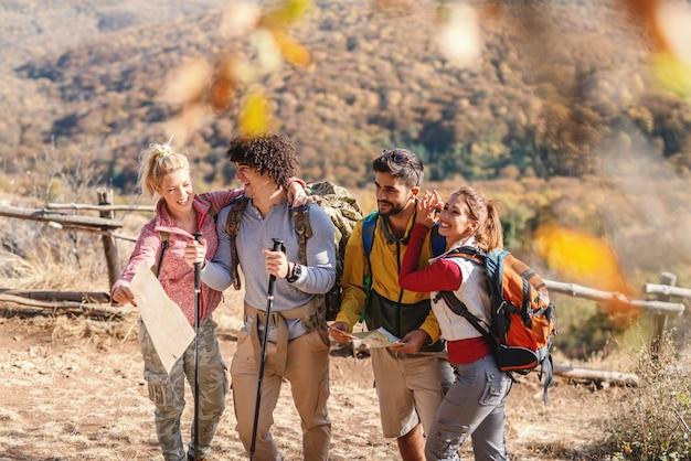 Vier gelukkige wandelaars staan op de glade en genieten van de natuur in de herfst.